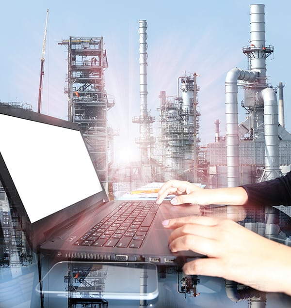 hand working on  laptop computer with oil refinery industry